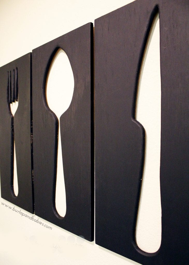 Wall art of large wooden cutouts of fork, spoon, and knife image.