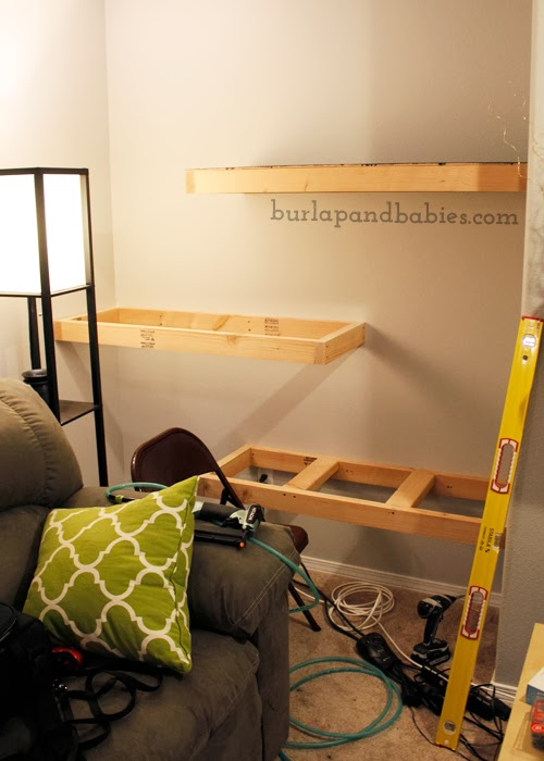 DIY unfinished wooden shelves attached to a wall image.