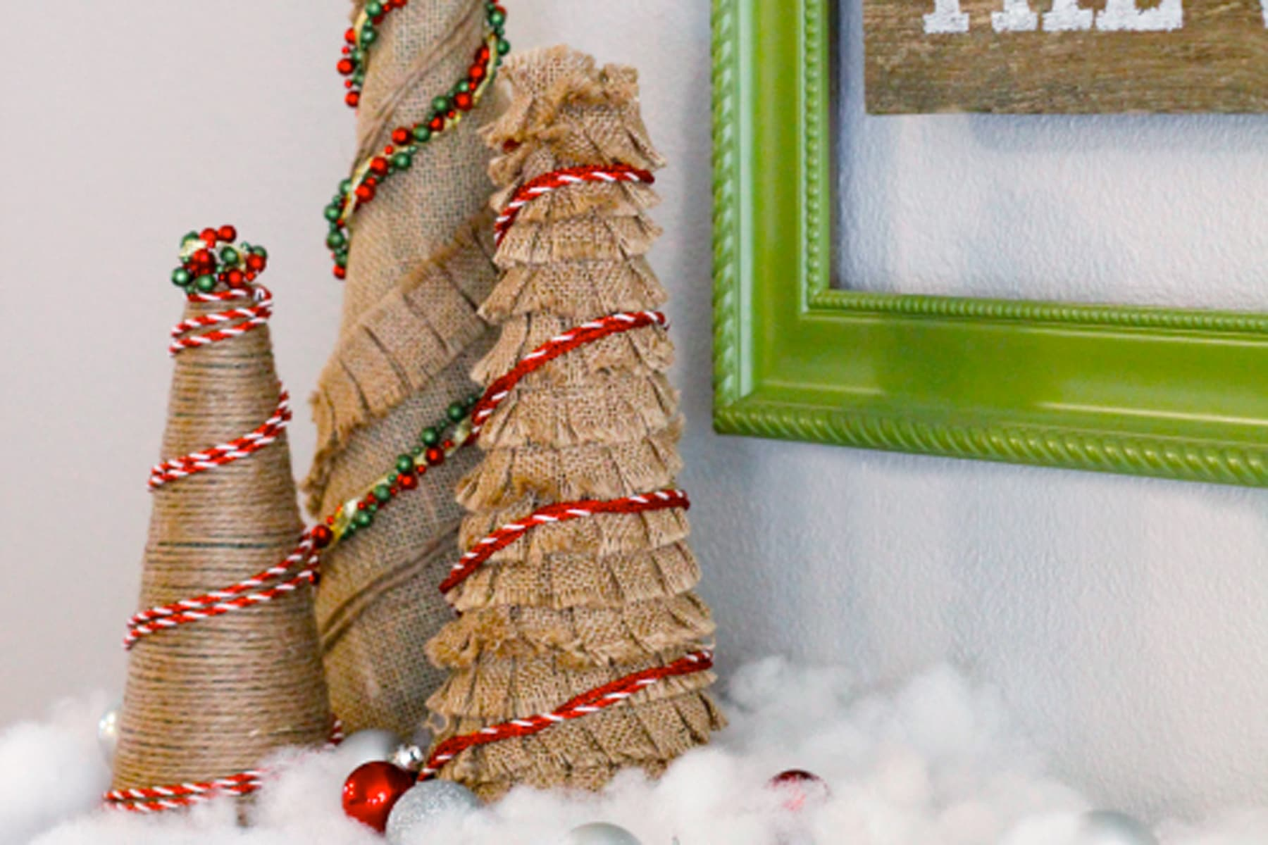 Mini Burlap Christmas Trees With Red Trim Against A Green Frame Image.