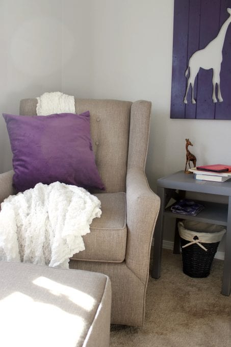 Chair in baby nursery with purple pillow image.
