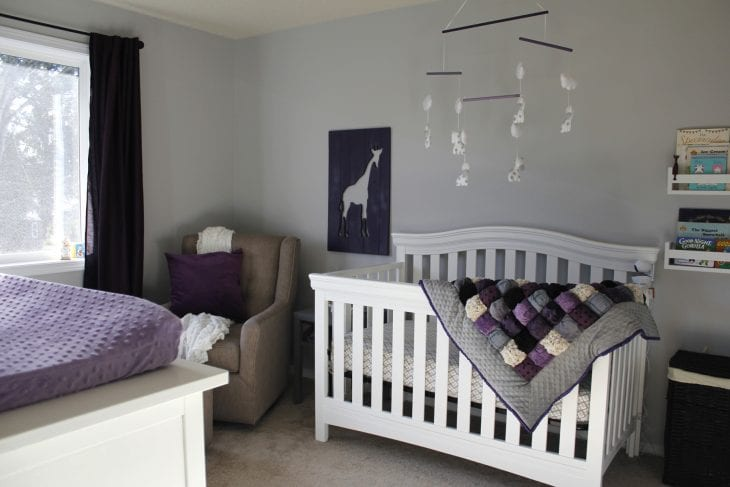 Purple baby nursery with purple puff quilt draped across white crib image.