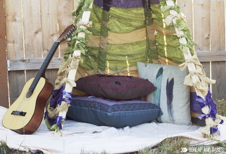 DIY No-Sew Teepee outdoors with pillows, blanket and guitar image.