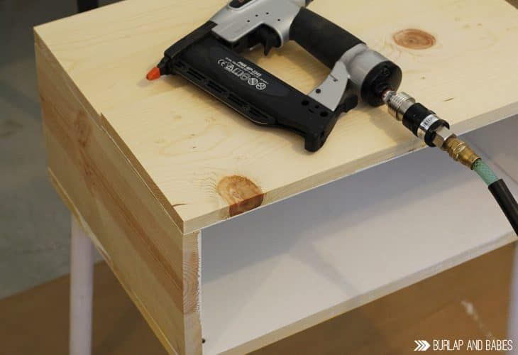 Power tool laying on top of unfinished wooden side table image.