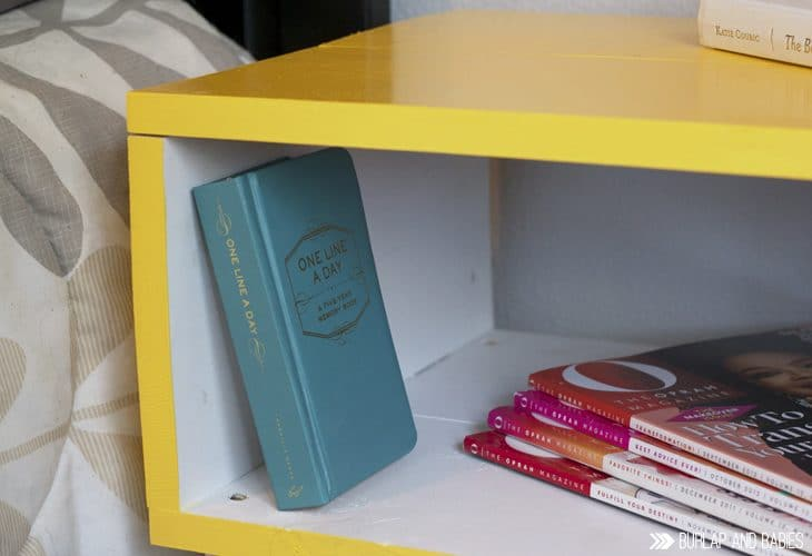 Yellow side table with book and magazines image.