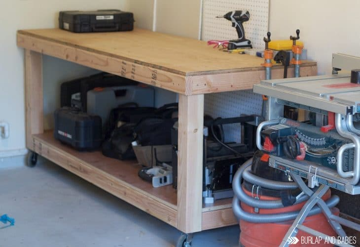 Rolling workbench made from wood sitting in a garage image.