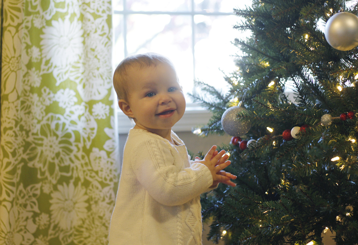 Happy Baby seeing the silver  and purple Christmas tree image.