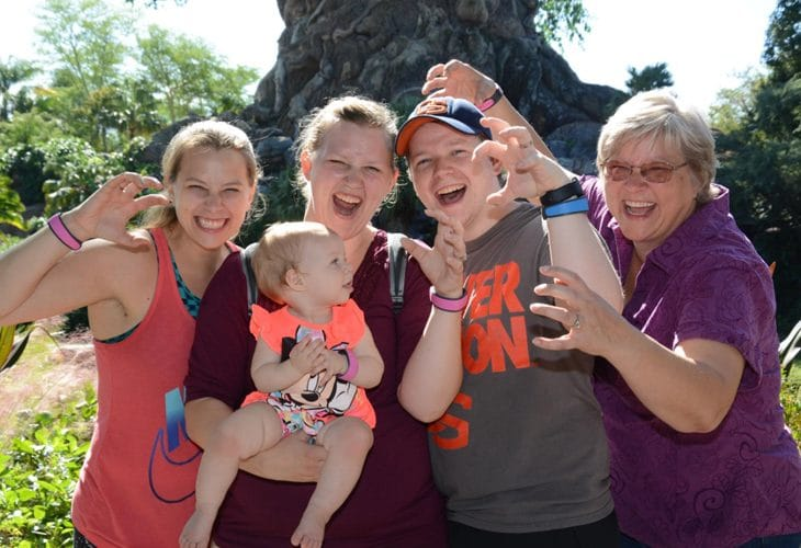 Happy smiling family with baby at Disney image.