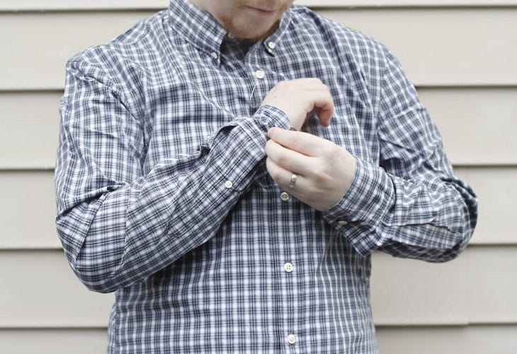 Man buttoning shirt cuff image.