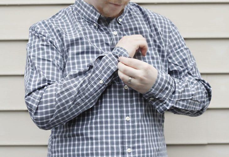 Man buttoning shirt cuff image.