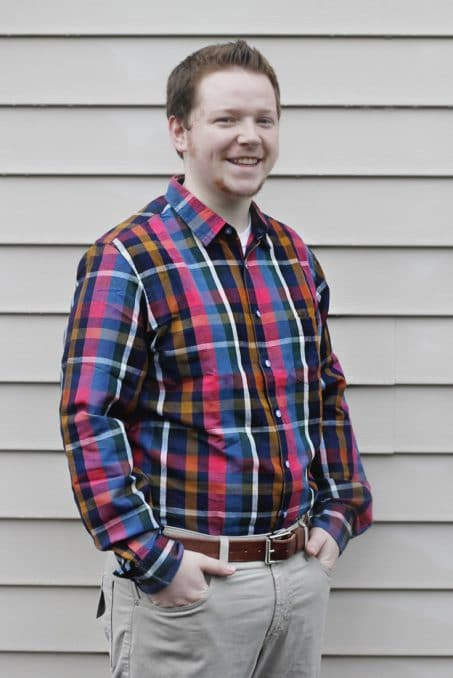 Man smiling in flannel shirt image.