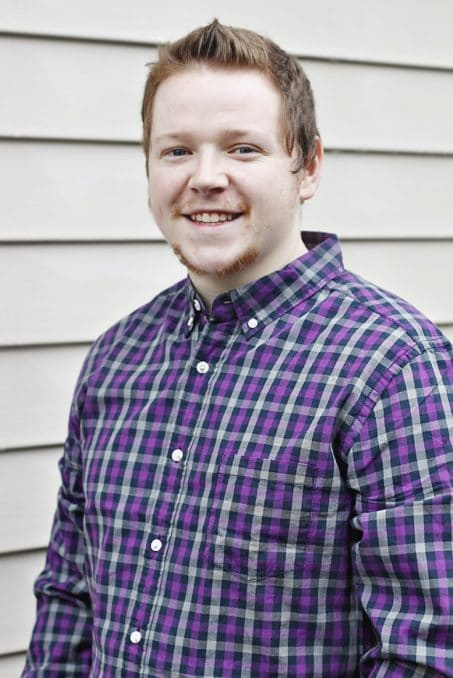 Man smiling in purple shirt image.
