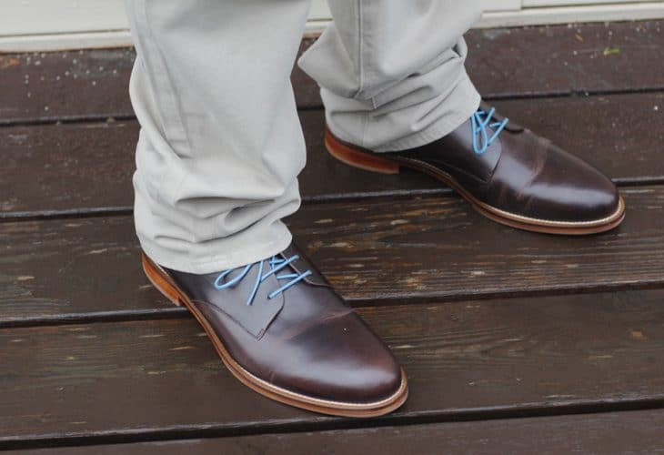 Man's brown shoes with blue laces image.