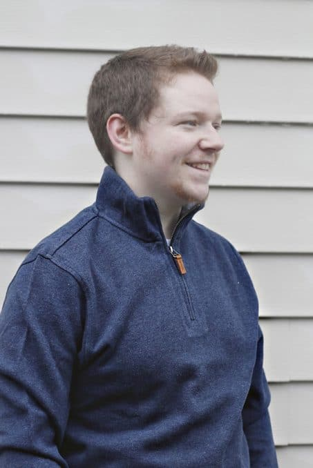 Man smiling in half-zip sweater image.