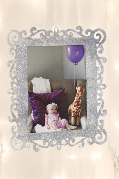 Sparkly silver frame with little baby on purple pillow image.