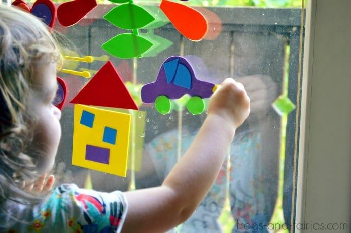Little girl putting shapes on a rainy window image.