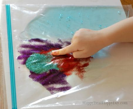 Child's hands playing with a plastic bag filled with tactile ingredients image.