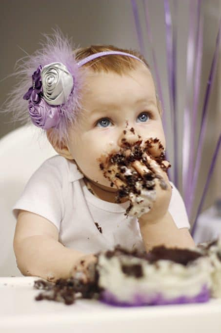 Little girl in purple headband with chocolate cake all over her face and hands image.