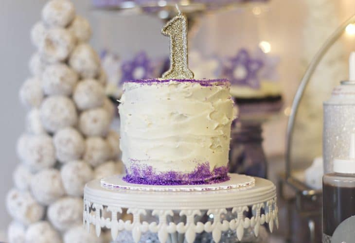 White 1st birthday smash cake with purple trim on cake plate image.