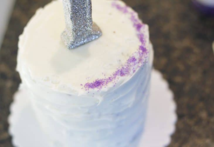 White cake with purple sugar in edges and 1 candle image.