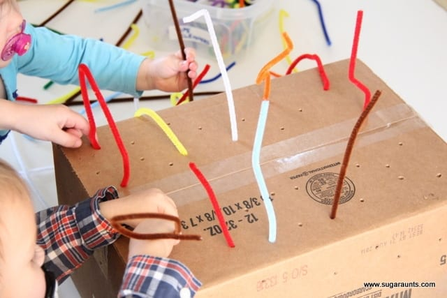 Children putting pipe cleaners in a box with holes in it image.