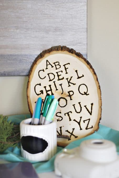 Wood with letters burned into it and clear jar with markets image.