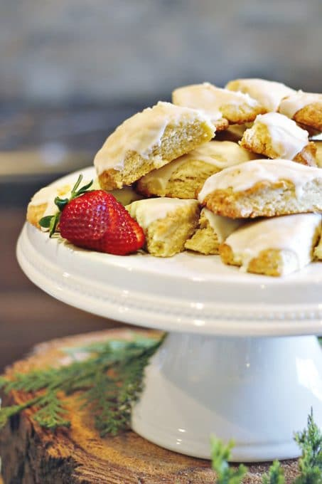 Scones displayed on a white cake stand with a strawberry accent image.