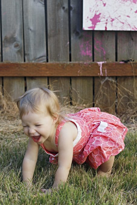 Happy little girl playing on the ground image.