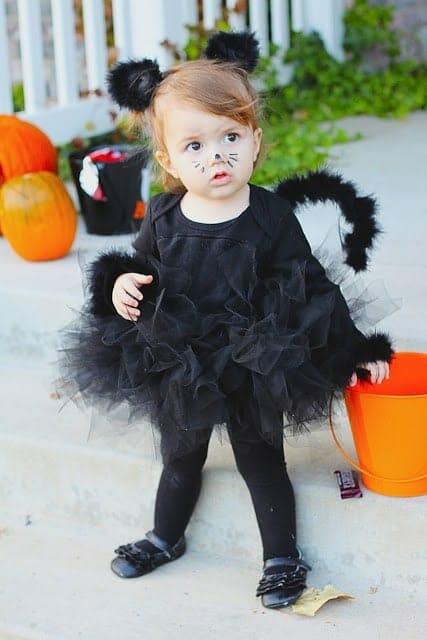 Little girl in DIY black cat costume image.