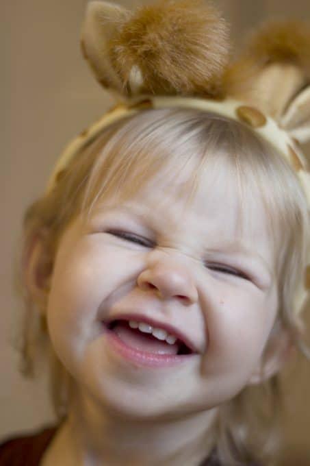 Smiling little girl in a giraffe headband image.