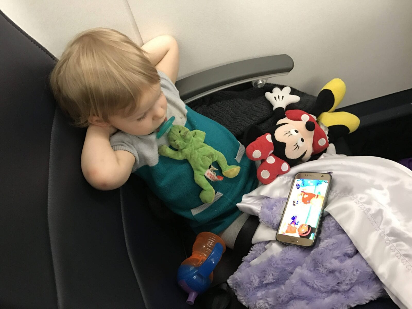 Child in airplane seat with Minnie Mouse image.