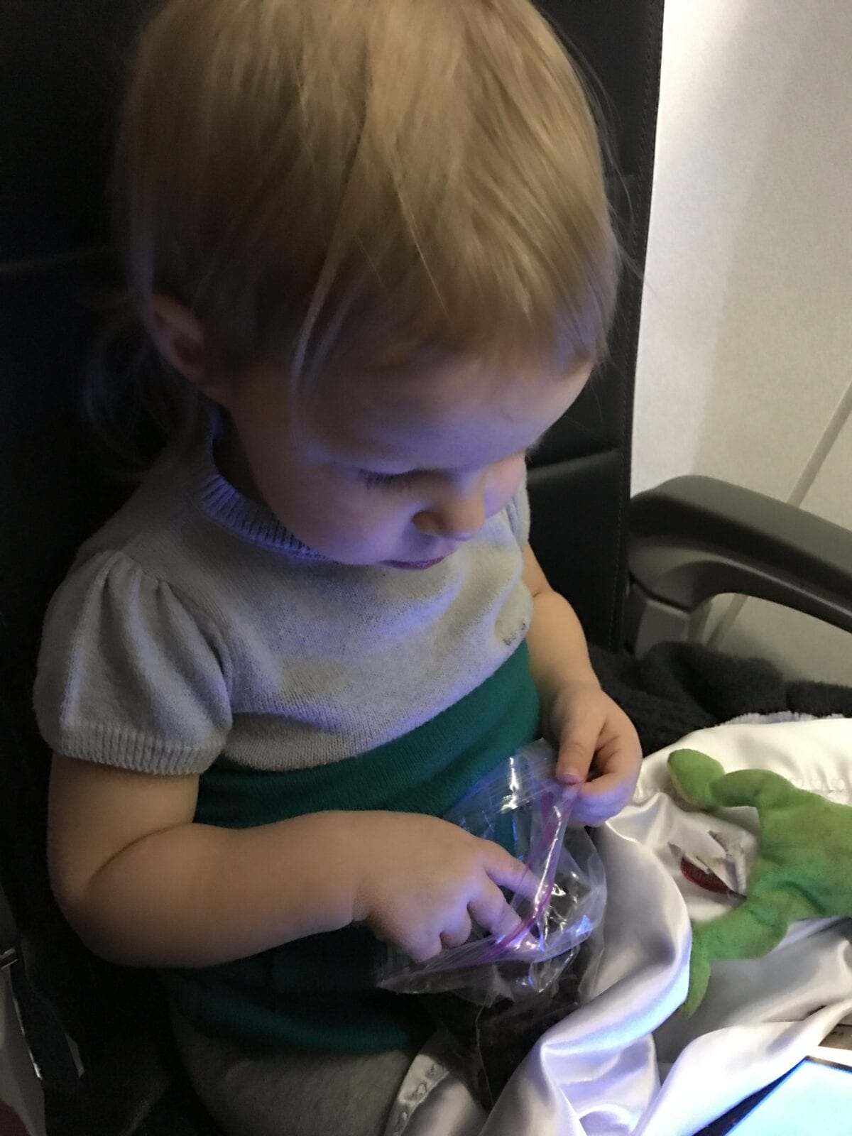 Child on plane eating grapes and watching iPad image.