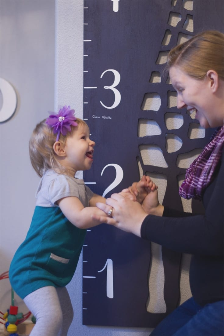 Little girl and Mom laughing in front of giraffe growth chart image.