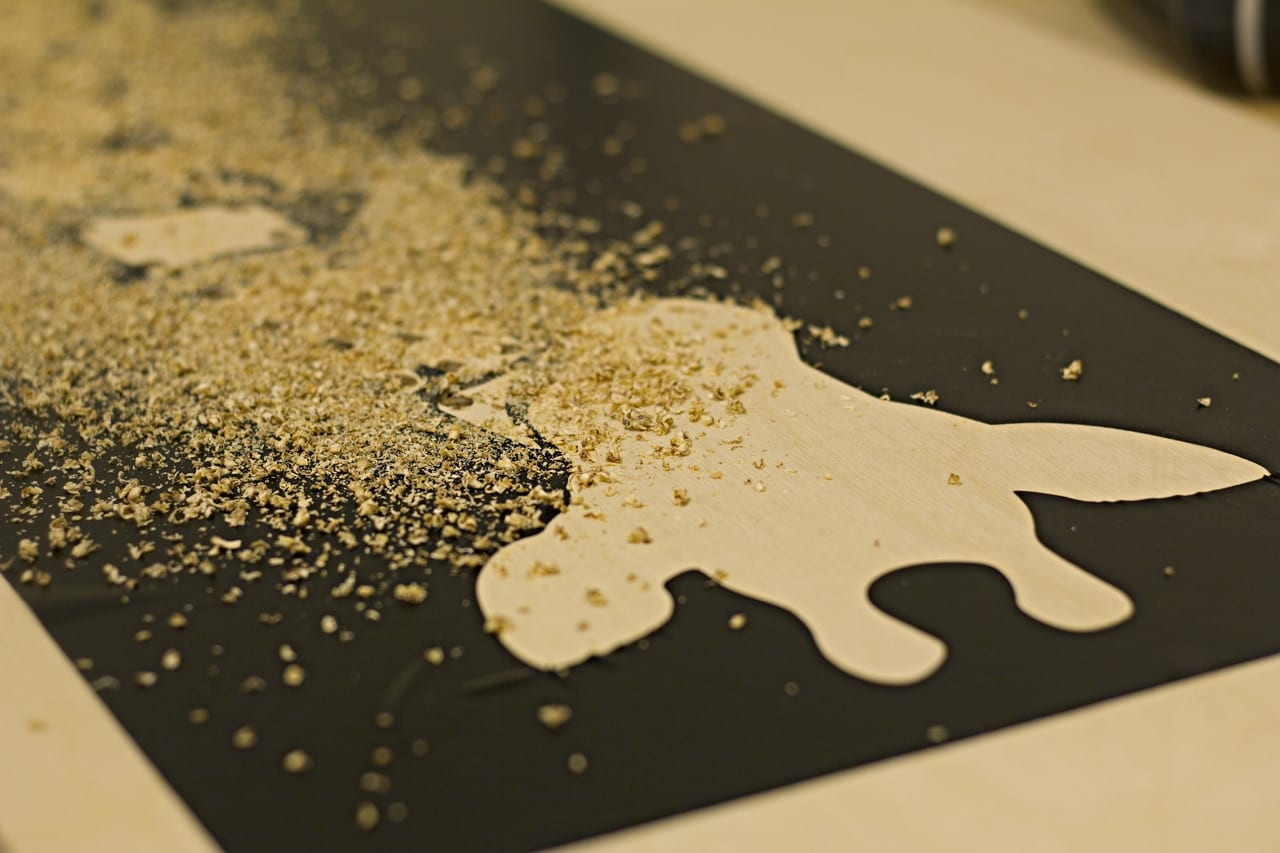 Sawdust covering a giraffe shaped stencil image.