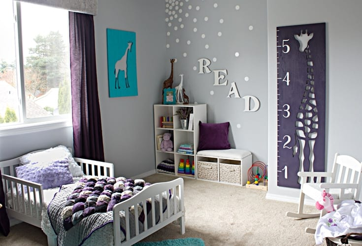 Little girl's purple bedroom featuring giraffe growth chart image.