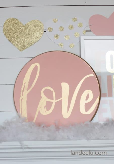 Pink round sign with the world love image.