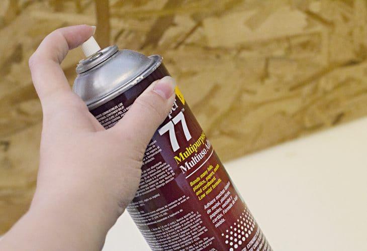 Hand holding spray adhesive image.