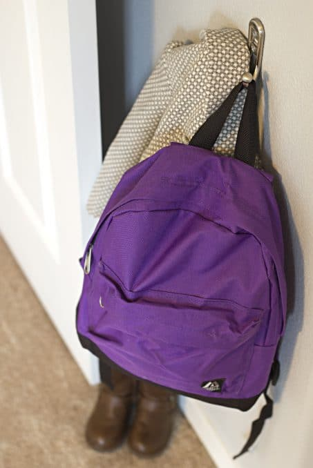 Purple backpack hanging on hook image.