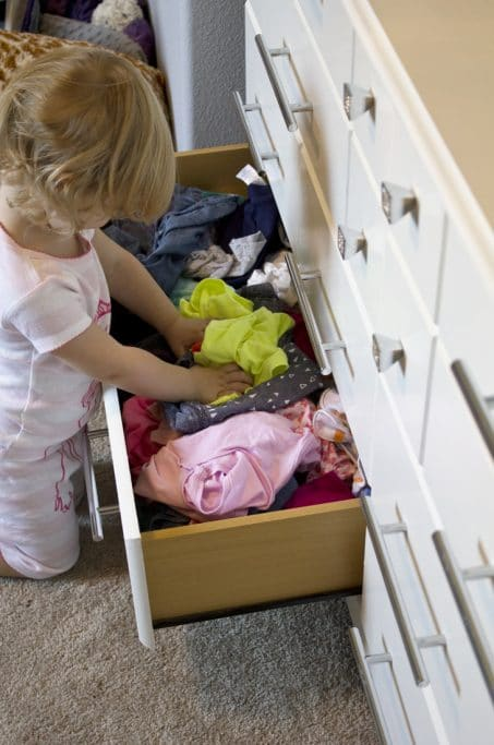 Child getting her clothes our of a drawer image.