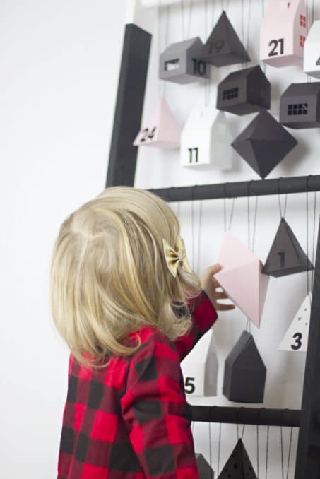 Make a modern advent calendar perfect for toddlers with this little paper village from Lia Griffith filled with activities and fun ideas for Christmas! This DIY ladder is the perfect way to display it all!