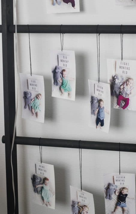 Monthly baby photos hung on a ladder for birthday party
