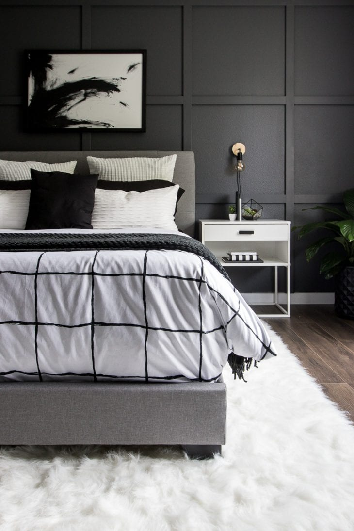 Monochrome modern bed with white faux fur rug image.