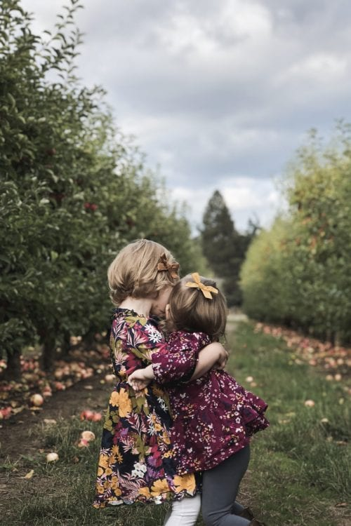 Image of hugging sisters in apple orchard